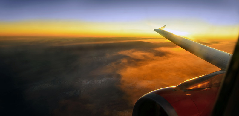 Jet engine and airplane wing at sunset over the Alps. Photo by Christian Wilkinson.