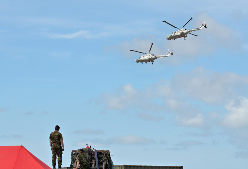 SOUTHPORT, ENGLAND - JULY 23: British Soldiers watch as Two Royal Navy Black Cats Lynx helicopters perform aerobatics and mid air stunts on July 23, 2011 in Southport, England.