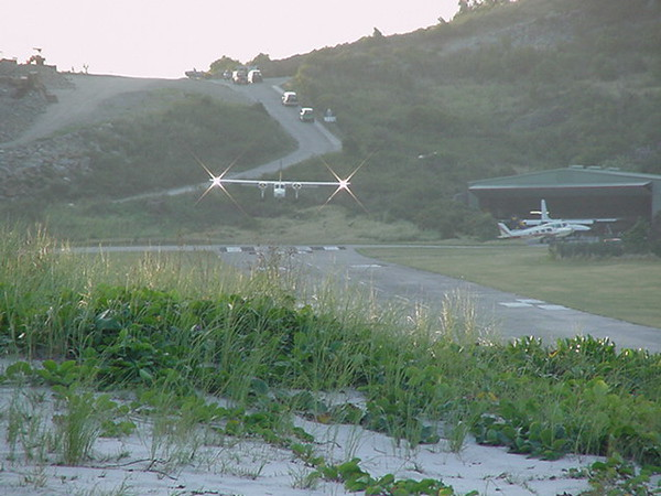 Planes landing a St. Barth swoop down a road ...