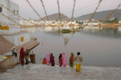 Ladies assembled on the banks of the lake for the evening aarti. The Pushkar lake is surrounded by hills on three sides and desert on the other side. The cave of Saint Agasthya was located on the snake mountain here. There is one belief that Kalidasa, the Indian counterpart of Shakespeare, had this place as his locale for his Sanskrit drama, Shakuntalam. According to a legend, the lake was formed when Lord Brahma dropped a lotus and wanted to perform a yagna. It has world's only temple of Lord Bramha (God of Creation). The Brahma temple located in Pushkar, Rajasthan is one of the important Hindu pilgrim centre.