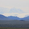 """Mt McKinley as officially refered to by the US goverment. The Athabaskas refer to the mountain as Denali or the """"High One"""". It is central to their sacred Raven story. The Raven, incarnated as a young man paddled his canoe to ask a woman to marry him. She refused, so he made her disappear by sinking her in mud. The woman's mother took revenge by having her two brown bears attempt to drown the man. The bears digged and created huge waves on the lake as the man paddled."""