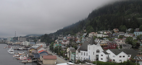 Ketchikan, Alaska.  It is the most southwestern city in Alaska and gets 230 days of rain per year.  Ketchikan is also home to the Alaska Marine Highway system.
