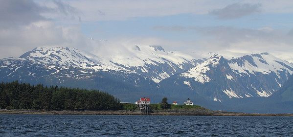As we motor out to see the Whales in Auck Bay, we pass a lighthouse dwarfed by the surrounding snow-capped mountains.