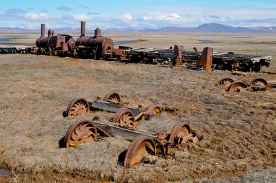These locomotives and flat cars are remnants of the unsuccessful attempt to build a railroad to gold mines near Council City, Alaska. A storm in 1913 destroyed the Solomon River bridge, stranding them here along Council Road, south of Nome. Cropped image.