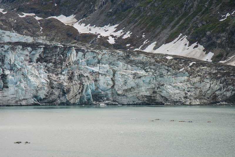 A string of kayakers paddling along base of glacier.