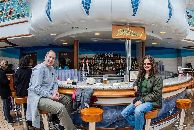 Rick's shot of Traci and me relaxing at one of the many refreshment stands (aka bars) on the ship.