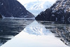 Approaching the Sawyer Glacier through floating ice, with a reflection of the mountains in the water.