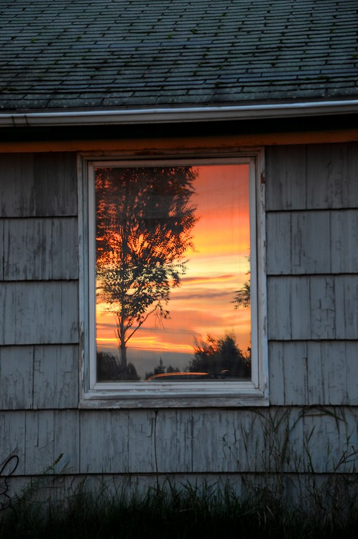 Sunset - Reflection - Anchorage - Alaska - USA<br /> This is one of those random photos that you sometimes get lucky enough to get. I was actually photographing the sunset, turned around and there was this abandoned house with a sheet over the window. The sunset was reflecting so well on the window, I just had to shoot it.