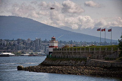 Brockton Point Lighthouse in Stanley Park with one of the many float planes flying overhead.