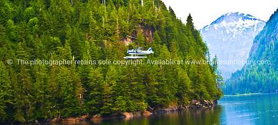Float plane flies low up an Alaskan fjord. SEE ALSO:   www.blurb.com/b/893025-north-to-alaska