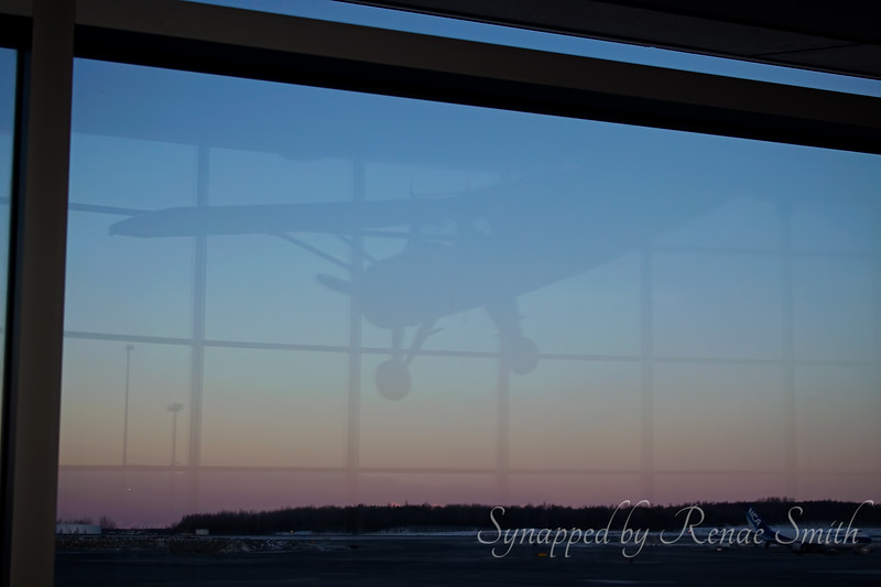 Waiting at the airport for our flight home.  A small plane suspended from the ceiling reflecting on the sunset...