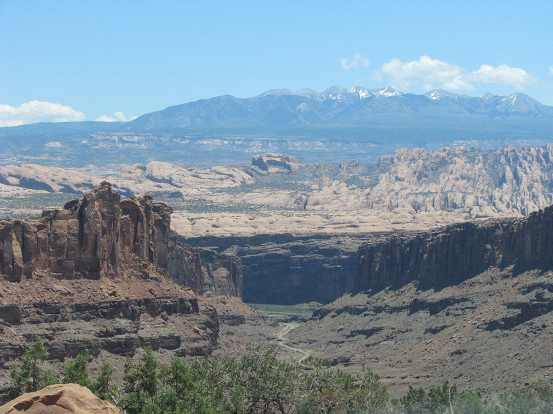 La Sal mountains in the distance and Long Canyon road snaking its way through the valley.