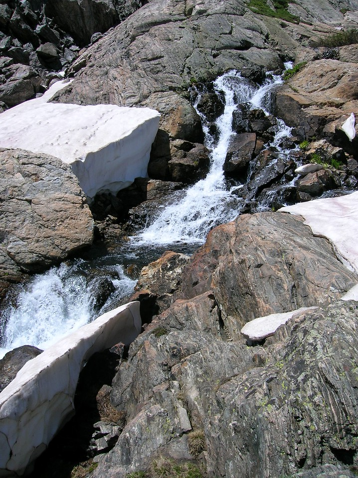 Mountain stream flowing through snow and rocks.