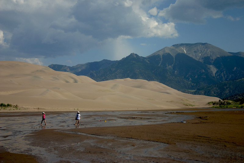 Playing in the stream in fromt of the Sand Dunes and Sangre de Cristo mountains