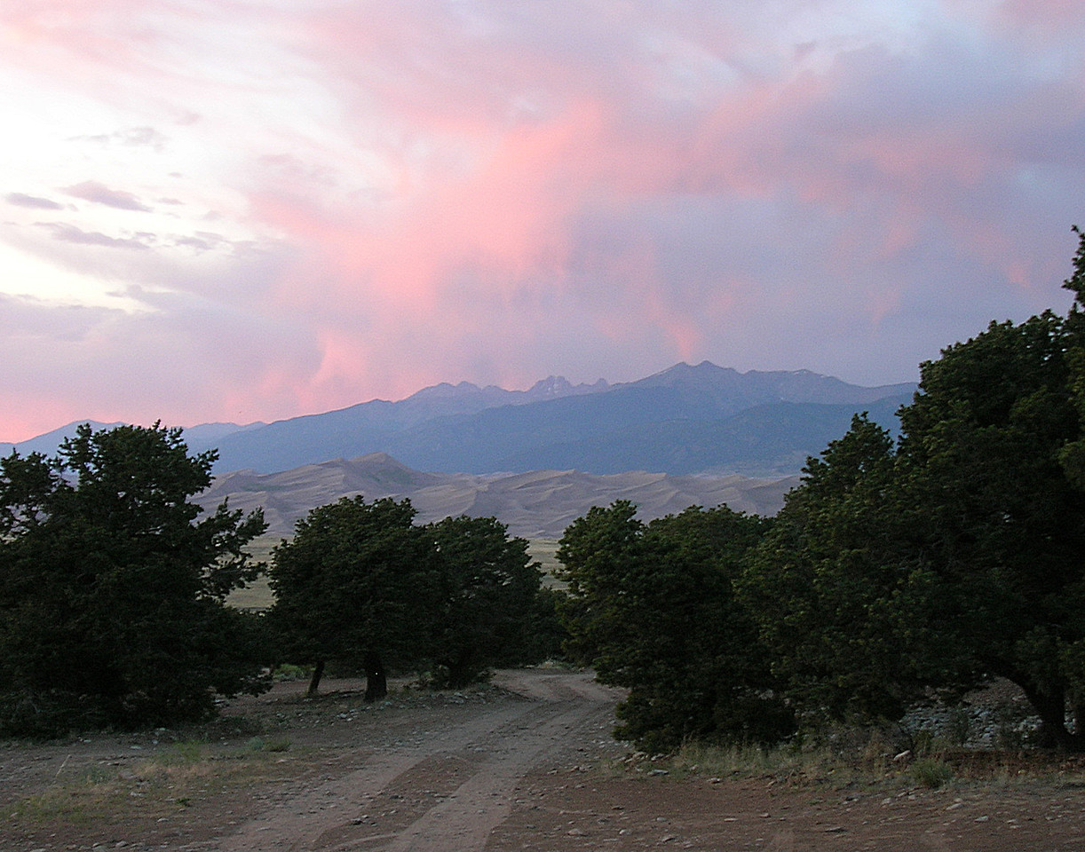 Evening in Colorado. Clouds above the landscape of trees, dirt auto tracks, sand and mountains.