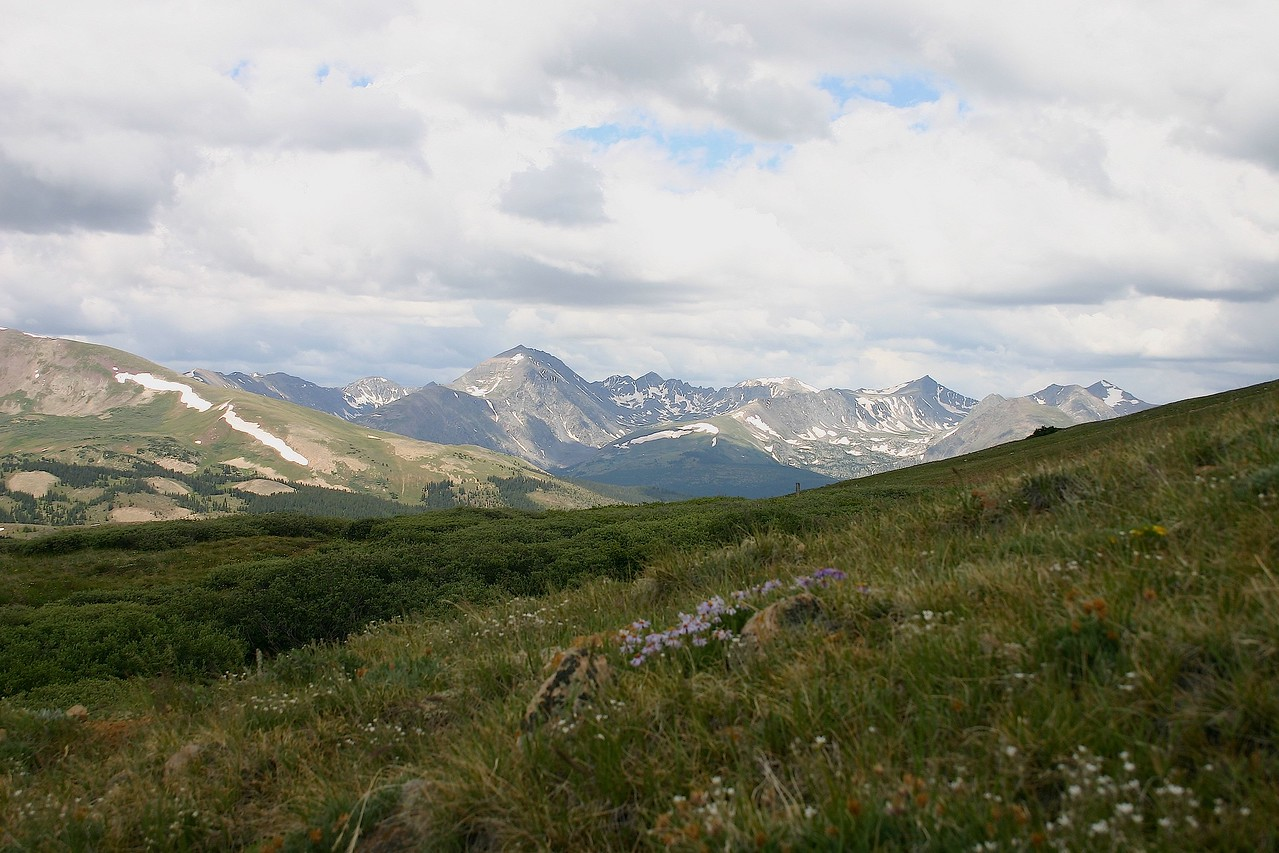 Storm brewing over alpine grassland with Gore Range as backdrop