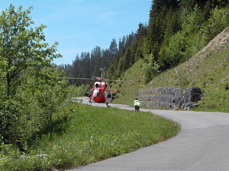 Helicopter rescue team landing on narrow mountain pass road. Col de la Croix in Switzerland
