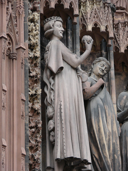 A man tempting a woman with an apple, on the exterior of the Strasbourg Cathedral.  Note the toads and vipers climbing up his back.