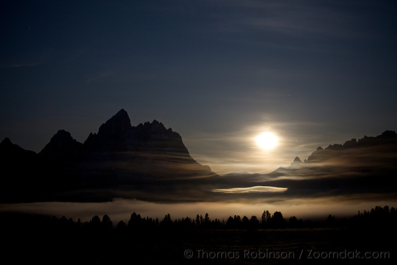 The moon sets through the clouds in the Grand Teton National Park.
