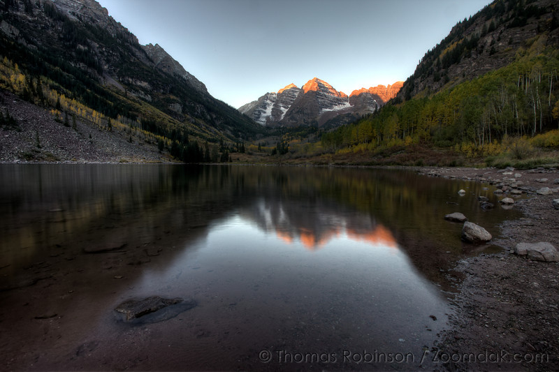 The Maroon Bells reflect the first light of sunrise off Maroon Lake near Aspen, Colorado. Both the south and north peak reach over 14,000 feet.