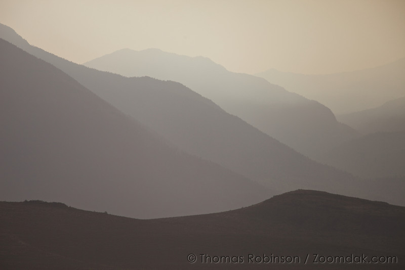 Mountains glow in the evening haze of a wildfire in the Umatilla National Forest region of Eastern Oregon.