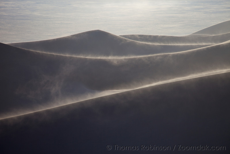 Wind blows sand across backlit dunes in the Great Sand Dunes National Park, Colorado.