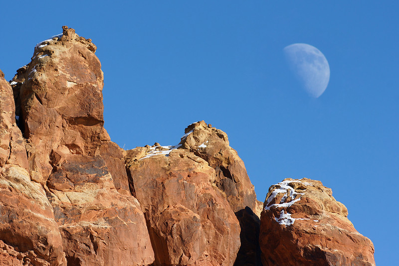The moon peeks over some of the sandstone fins.