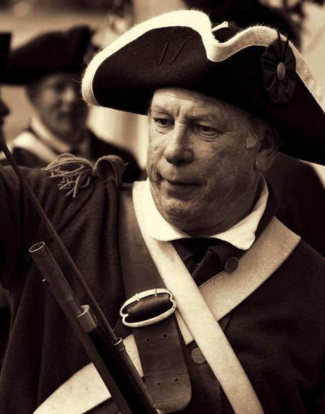 American Village Colonial Sodier Loads Musket in Preparation of Battle