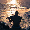 Silhouette of Bare Chested Violinist Playing Outdoors Contrasting With Shine Waters at Sunset