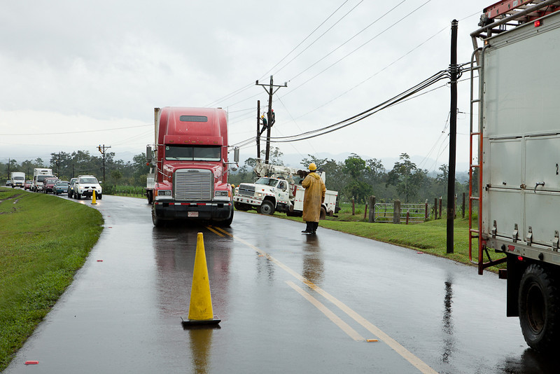 18 wheeler pulling a utility truck out of the mud.