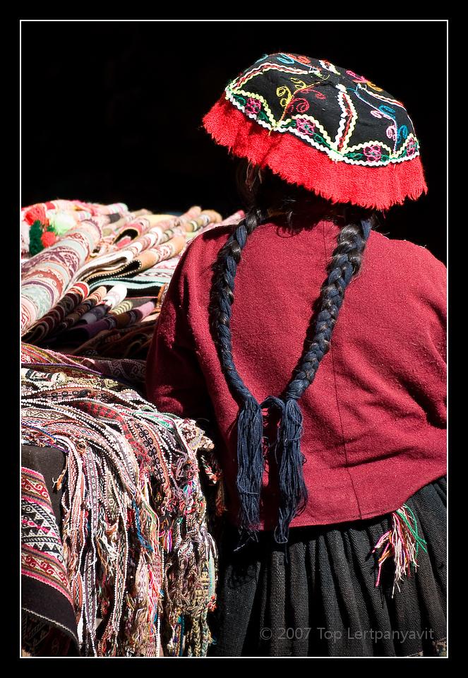 Andean seller peddling fabric weavings