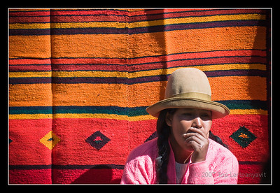 A native Andean street vendor contemplates in front of a colorful Andean rug at the Pisac market
