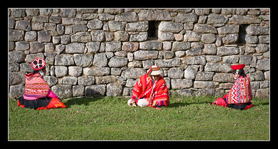 Andean natives sit and wait at Machu Picchu