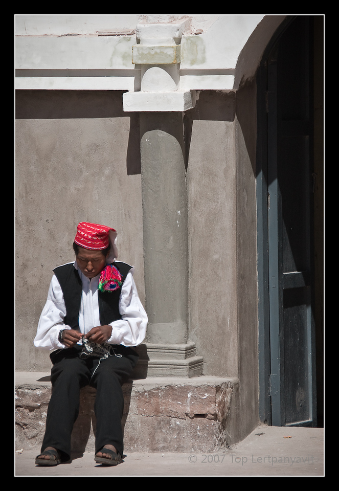 Taquile man knitting at the entrance to a church. Based on the white tip of his chullo (hat), he is single