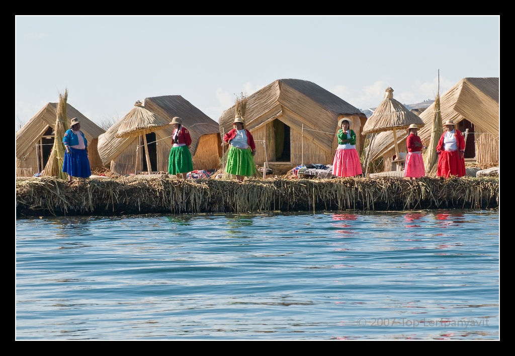 Women on the Uros island of Santa Maria wait for tourist boats to visit