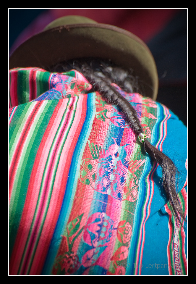 An Andean native carries a colorful shopping wrap at the Pisac market