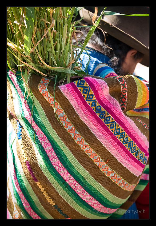 An Andean native carries a colorful shopping wrap filled with reeds at the Pisac market