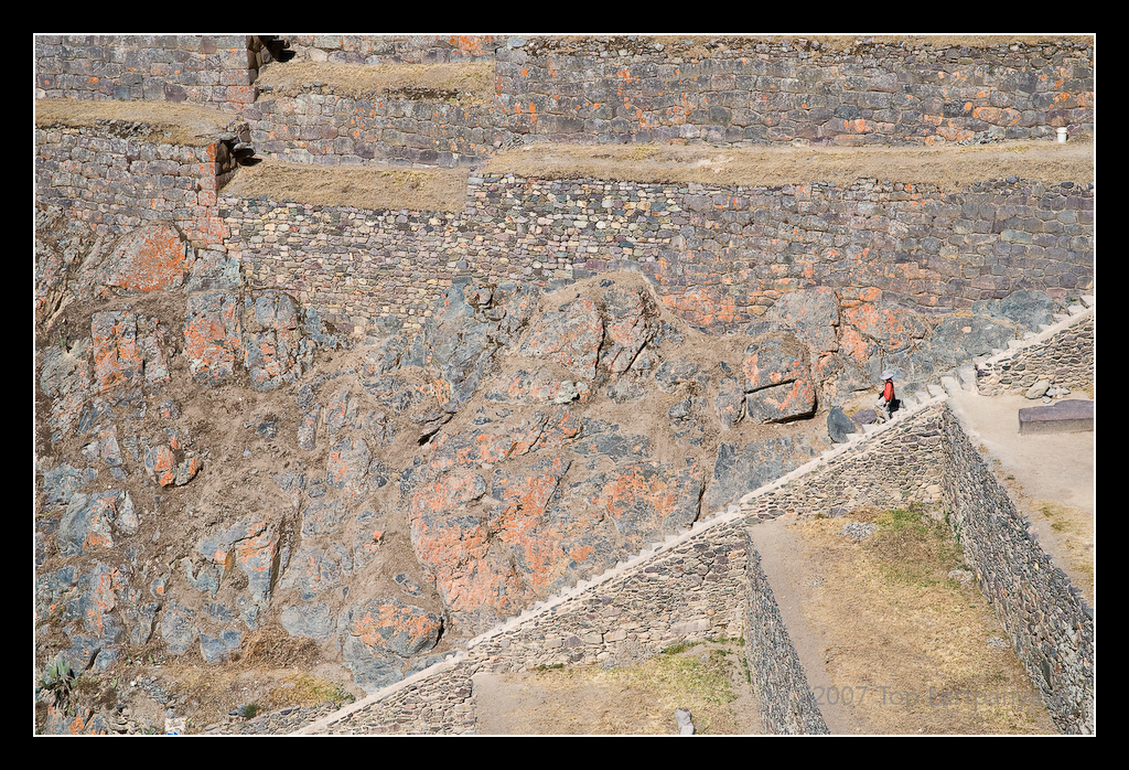 A visitor descends the steps of the Ollantaytambo ruins