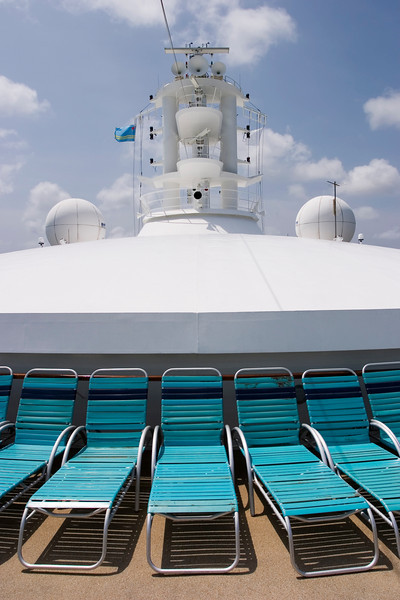 A line of desk chairs in front of the bridge and main mast of a cruise ship. The twin radar domes are flanking the mast.