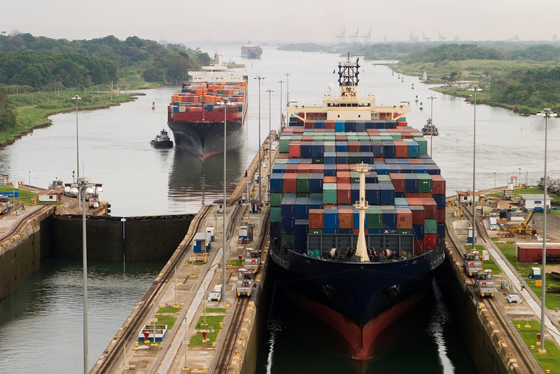 Several freighters, assisted by tugboats, are entering the Panama Canal at Gatun Locks on the Atlantic side. These container ships are fully loaded with cargo heading west towards the Pacific.
