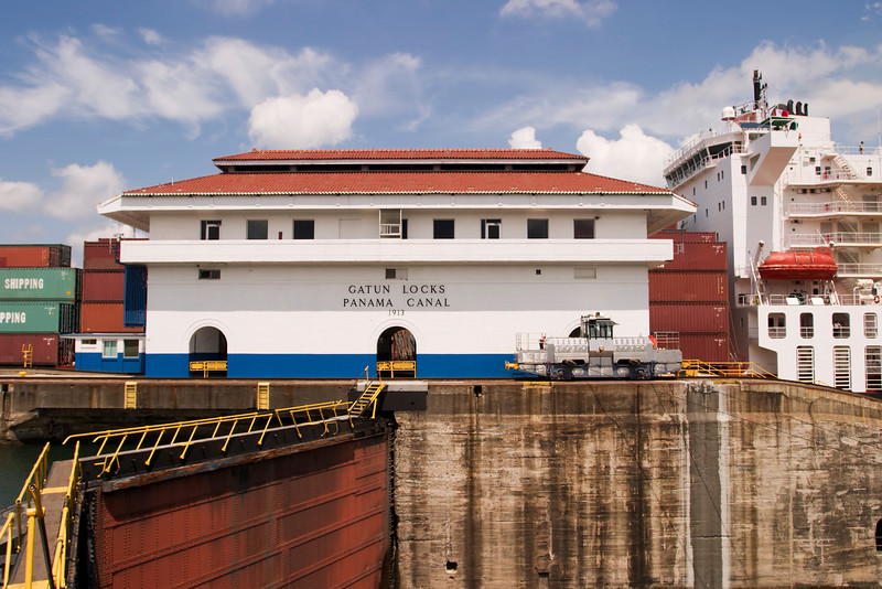 One of the main buildings at Gatun Locks in the Panama Canal with a large container ship full of cargo in the background.