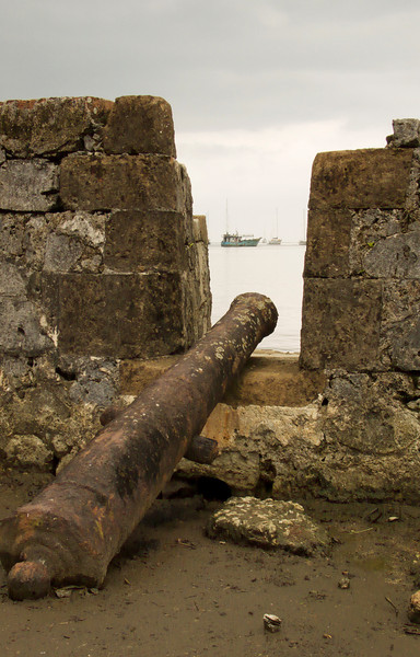 A single rusty cannon pointing towards a harbor filled with boats. This old fort protected the harbor.