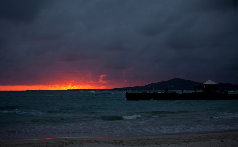 A pier against the horizon with a fiery birght red and orange sunset as the light goes down over the horizon in the Galapagos Islands of Ecaudor