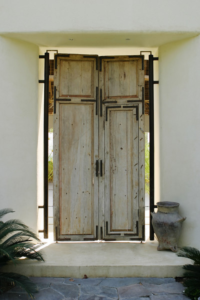 An antique wood front door for a Mexican house. The light from the open-air courtard behind is splashing around the edges of the door.