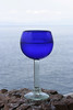 A cobalt blue glass goblet is illuminated in front of the Pacific Ocean. The condensation from the lemonade inside has condensed lightly on the outside of the glass.
