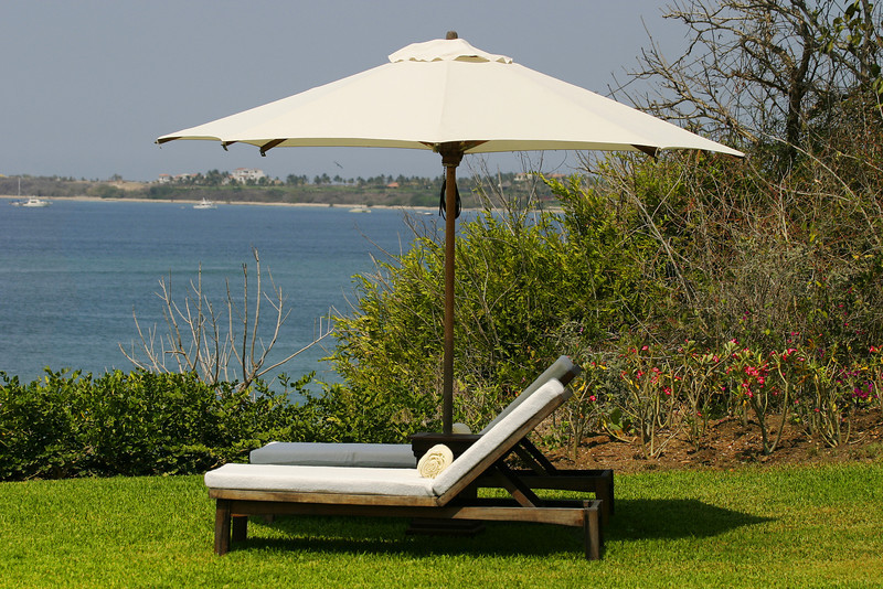 A large white beach umbrella shades a chaise lounge chair that is overlooking the Pacific Ocean near Puerto Vallarta. This calm and relaxing scene captures the relaxed atmosphere of vacation and travel in the warm and sunny tropics.