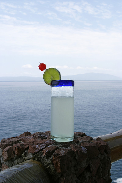 A tall glass of lemonade with a slice of green lime and a bright red cherry in front of an ocean view in Puerto Vallarta. The cool drink in the tropical climate has resulted in drops of condensation on the outside of the glass.