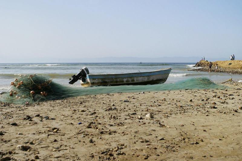 A small fishing boat with an outboard motor pulled up on the beach with its net laid out in front. This small skiff was typical of the boats seen around fishing villages in Mexico.