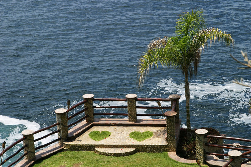 A romantic setting for two people that is formed by two hearts of grass built into a rock promontory over the ocean.