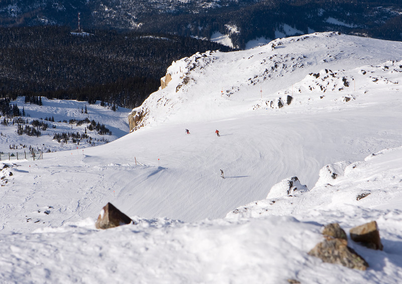 A view of one of the ski runs from the summit of Whistler Mountain with just three people visible in the middle of the slope.
